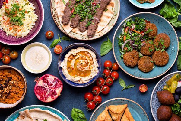 71416991 - middle eastern or arabic dishes and assorted meze, concrete rustic background. meat kebab, falafel, baba ghanoush, muhammara, hummus, sambusak, rice, tahini, kibbeh, pita. halal food. lebanese cuisine