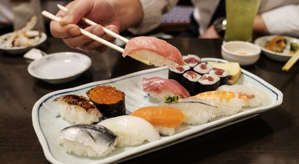 Chopsticks holding a piece of Tuna sushi above a full plate of various nigiri and maki sushi.